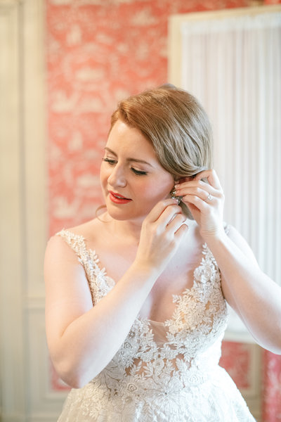 red head bride puts in her vintage earrings wearing a lace wedding dress