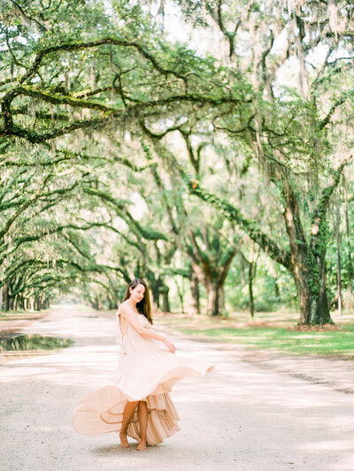 Pregnant woman spins under a tree-lined path during maternity portraits