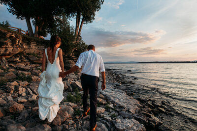 bride and groom walking over rocks on shore