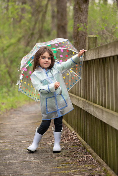 Little girl on bridge in raincoat & boots holding umbrella