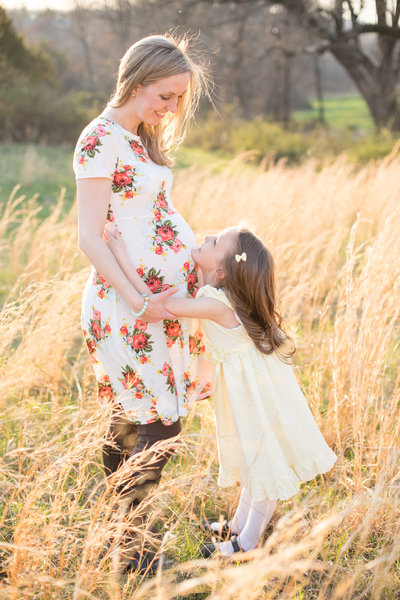 Maternity photo of mother and daughter in a beautiful field at sunset
