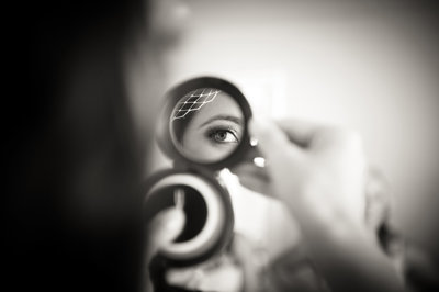 Bride-looks-in-mirror-fixes-makeup-San-Diego-CA-Paradise-point