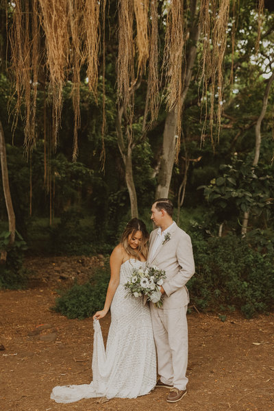 bride and groom standing in front of trees
