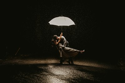 bride standing in the rain holding an umbrella and being dipped by the groom during wedding portraits