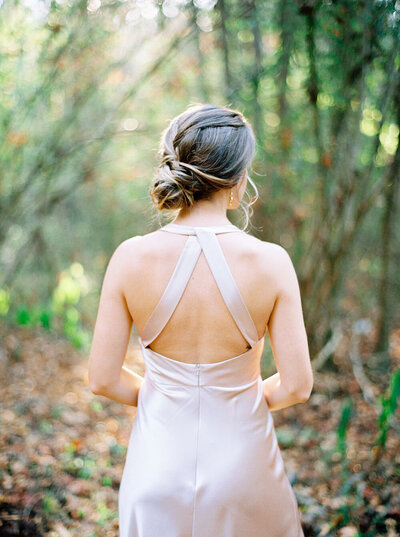 Loose twisted bridal updo with a silk blush wedding dress