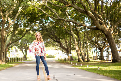 high school senior girl poses for senior portraits in tree lined street