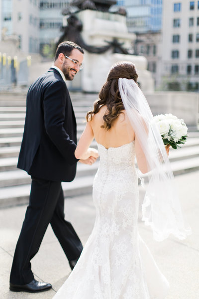Bride and groom walking portrait in downtown Indianapolis taken by wedding photographers Ivan & Louise.