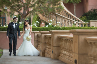 Bride and Groom walking down a pathway at the Fairmont Grand Del Mar