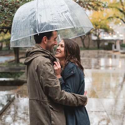 Couple snuggles under an umbrella on a rainy day at the Art Institute of Chicago South Gardens