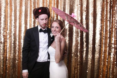 bride and groom posing with an  umbrella on a shiny gold backdrop