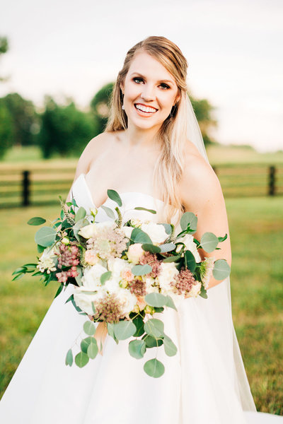 bride smiles while holding bouquet