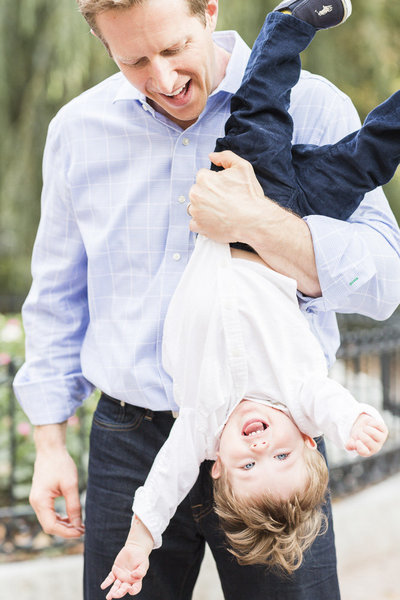 dad holding son upside down and child is laughing