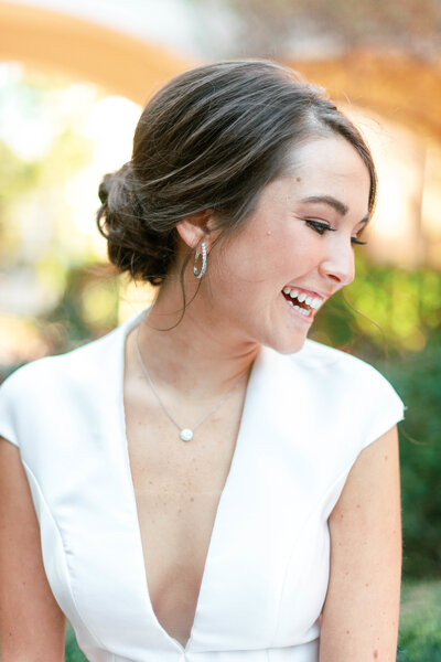 A happy bride on her wedding day with a beautiful updo and makeup