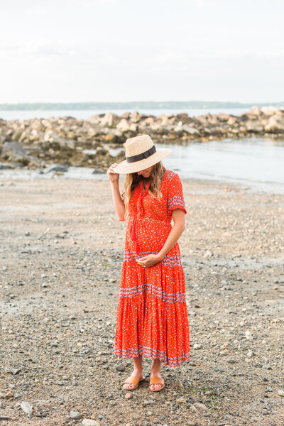 pregnant woman wearing a straw hat looking at her belly