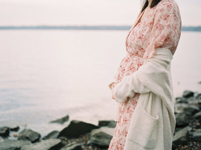 Mother holding her belly by the water during Alexandria maternity session
