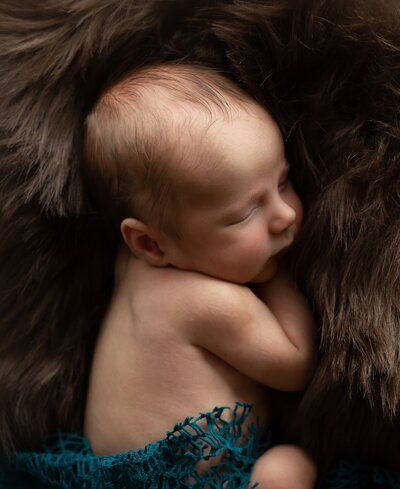 Beautiful newborn baby sleeping on brown fur blanket