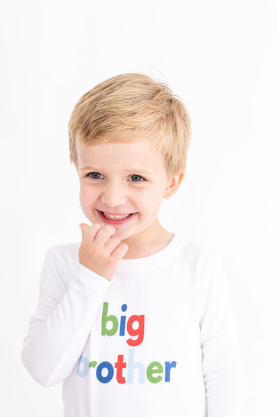 "Little boy wearing a white shirt that says ""big brother"""