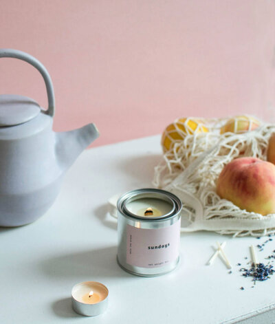 Scented soy wax candle by Mala the Brand. Sundays scent. Wooden wick candle with matches, a kettle and peaches.