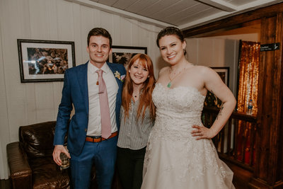 bride and groom smiling with woman standing between them