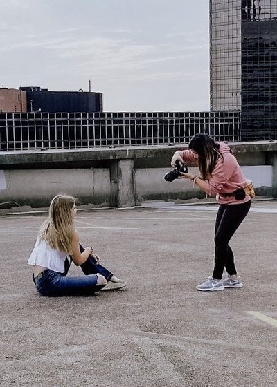 woman taking picture of girl sitting on ground