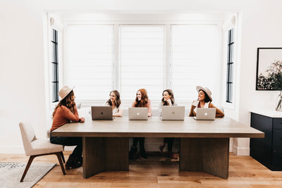 women sitting at table with laptops
