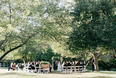 Lush green ceremony location. Bride and groom are getting married with a celebrant. There is a rustic wooden arch above them. This beautiful outdoor wedding took place at John James Audubon Center.