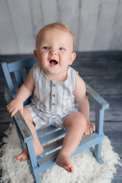 one-year old sitting on chair and smiling in studio