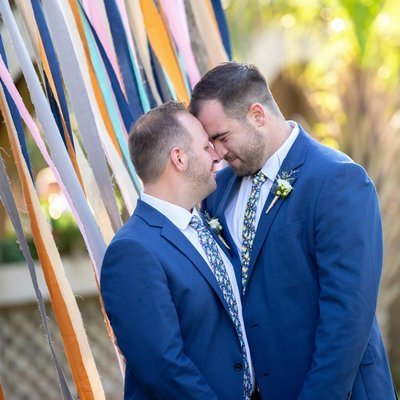 Two grooms hold each other close on their wedding day