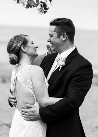 Bride and groom embrace at their Presque Isle beach wedding