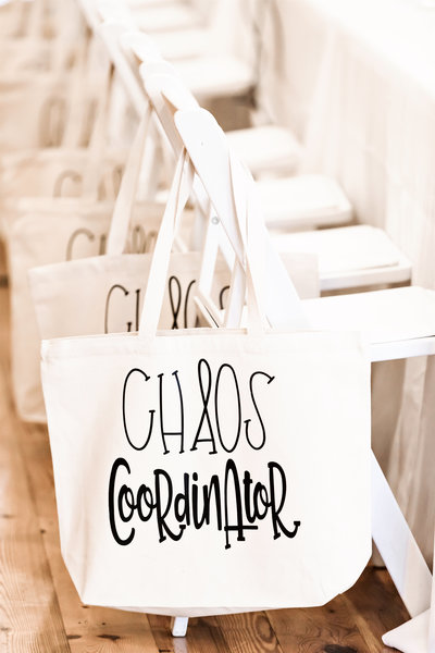Chaos Coordinator tote bags hanging on backs of white chairs at Refine for Wedding Planners Retreat