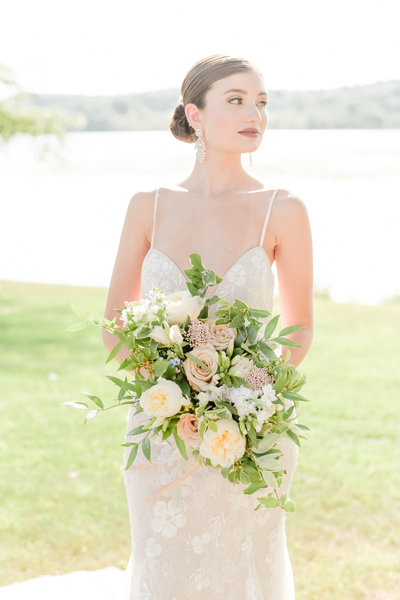 Bride holds bouquet in front of lake