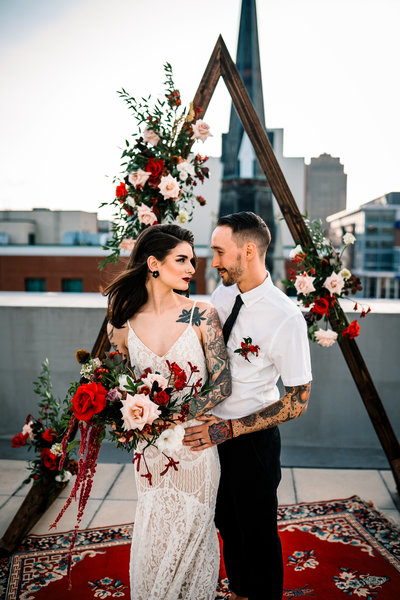 Bold, edgy floral design with deep reds and white flowers. Triangle flower arch for a rooftop ceremony.
