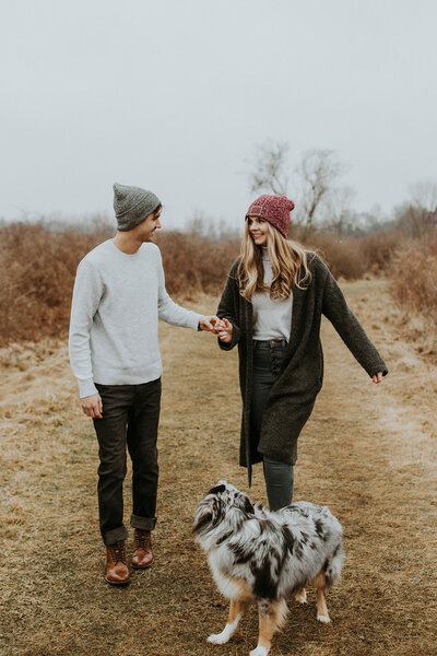Shanea and Dylan walking with their dog and  holding hands