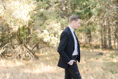 groom in field standing with his hands in his pocket and looking at the ground