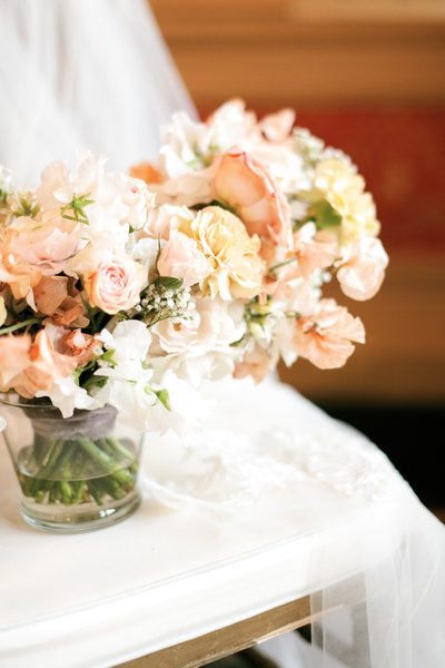 white pink and pastel flowers in a close up shot of a bridal bouquet by roots floral design styled on a chair at the brown hotel wedding in louisville