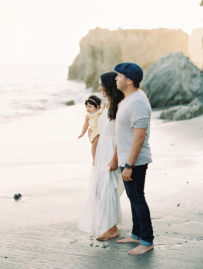 A family holds hands on El Matador beach in Malibu during their family portrait session with photographer Daniele Rose