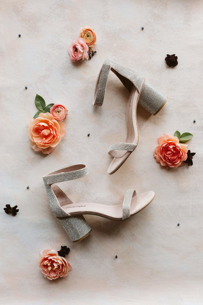 shoes and coral flowers on ground