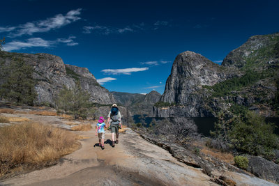 A dad hikes with his children  through the Hetch Hetchy valley in Yosemite