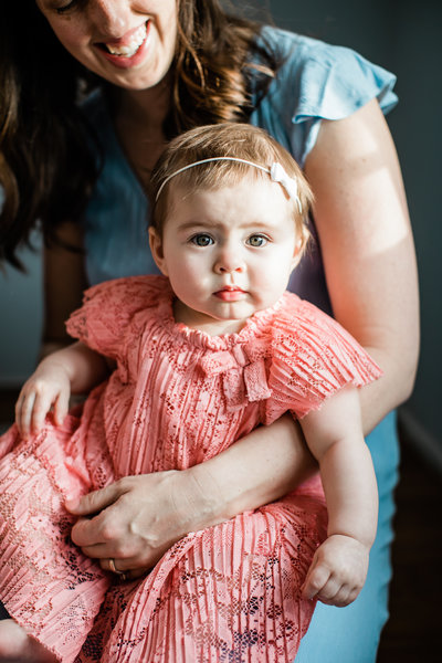 Woman holding baby girl in peach dress