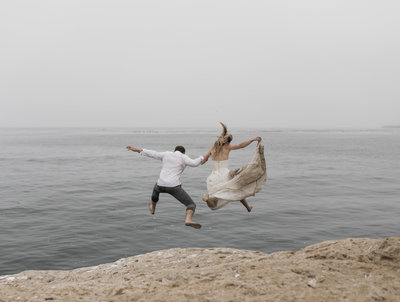 bride and groom jumping from rock into water