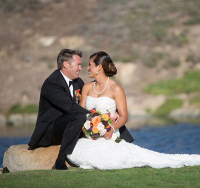 Bride and Groom sitting on rock at The Crossings at Carlsbad wedding venue