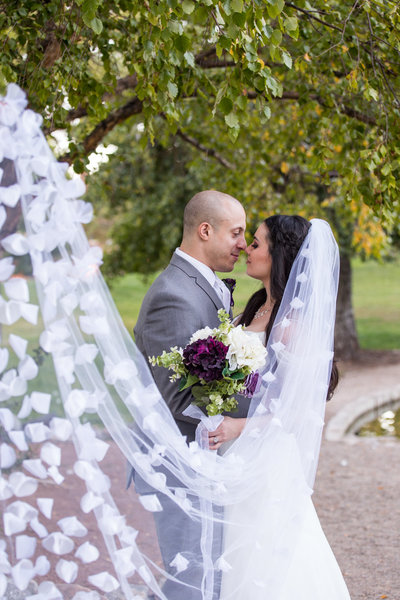 Bride and groom kissing behind long veil