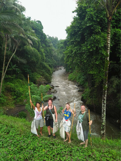 4 people picking trash by a river in Bali