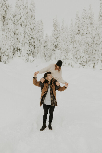 Girl sitting on boyfriends shoulders holding hands in the snow