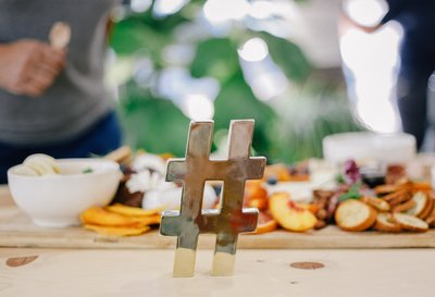 A small golden paperweight in the shape of a hashtag, displayed in front of a large charcuterie board of fruit, nuts, cheeses, and meats.