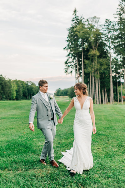 Virginia Wedding Photographer, bride and groom walking hand in hand in the grass