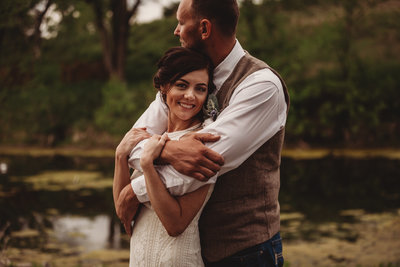 groom wraps around his bride in front of a pond in Kansas after their barn wedding ceremony | Native Roaming