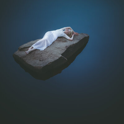 Fine Art Work of a woman lying on a stone in the water