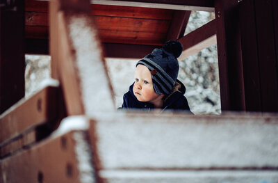 little boy in tree house during a snowstorm.