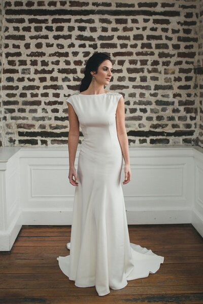 Model wears the Tamarisk wedding dress with a high bateau neck in all crepe
